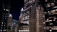 Wide shot tilt down AI Building, Chase Manhattan Tower, Liberty Tower and Federal Reserve Bank at night / NYC