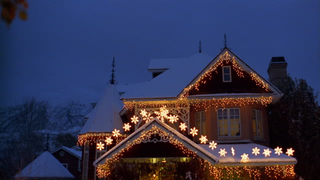 Wide shot tilt down exterior of snow-covered house decorated with Christmas lights / light in window going out