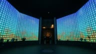 Wide shot tilt down Glass Buddha statues illuminated by lightemitting diodes sit inside the Ruriden columbarium at the Koukokuji temple in Tokyo...