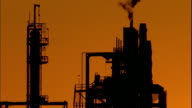 Wide shot tilt down silhouetted oil refinery and smokestacks at dusk / San Pedro, California