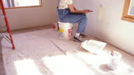 Wide shot tilt down tilt up woman in overalls sitting on bucket and painting wall