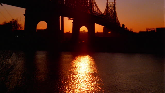 Wide shot tilt up silhouetted 59th Street Bridge over East River at sunrise / New York City