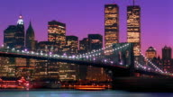 Wide shot time lapse boats on East River with Brooklyn Bridge and World Trade Center / dusk to night / New York City