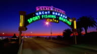 Wide shot time lapse cars entering and exiting Santa Monica Yacht Harbor with neon sign over road / California