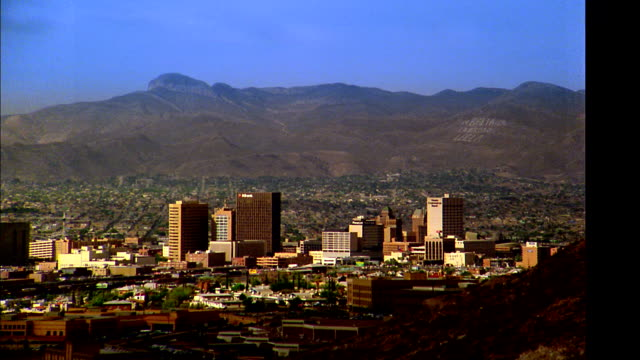wide shot time lapse cloud shadows passing over El Paso with mountains in background / Texas
