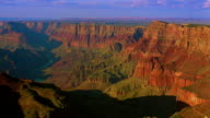 Wide shot time lapse clouds above and shade enveloping Grand Canyon from day to dusk / Arizona