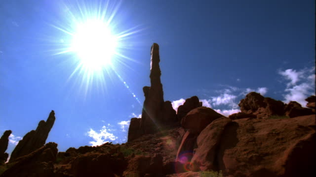Wide shot time lapse clouds and sun moving behind rock formation / Monument Valley