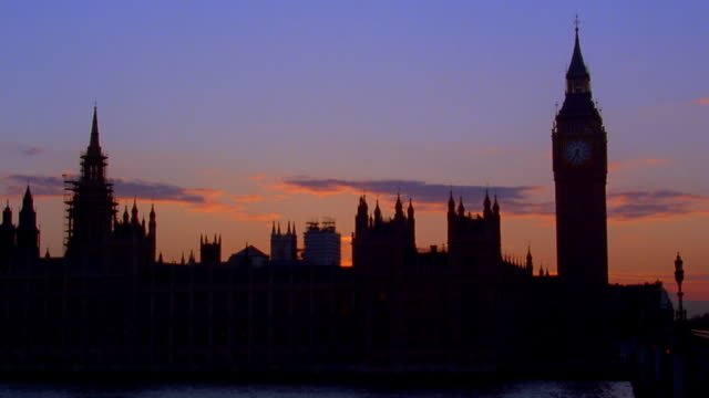 Wide shot time lapse clouds rolling behind Big Ben and Parliament with Thames River in foreground at dusk / London