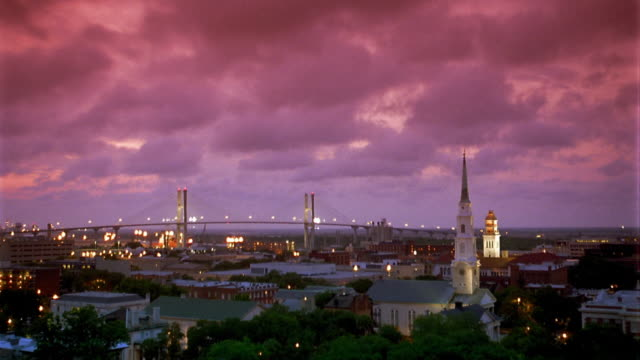 Wide shot time lapse clouds rolling over Savannah with Talmadge Memorial Bridge in background at dusk / Georgia