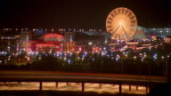 Wide shot time lapse ferris wheel at Navy Pier with traffic in foreground at night / Chicago