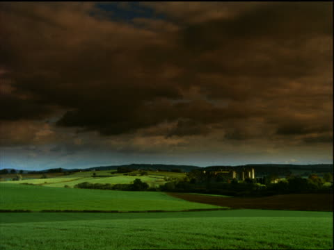 wide shot time lapse storm clouds over green countryside + Raglan Castle / England