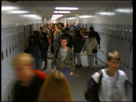 Wide shot time lapse students entering school hallway / getting into lockers