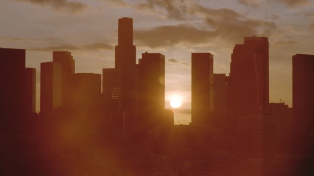 Wide shot time lapse sun rising behind silhouetted skyline / downtown Los Angeles