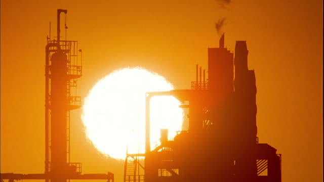 Wide shot time lapse sun setting behind silhouetted oil refinery with smokestacks / San Pedro, California