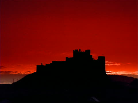 wide shot time lapse sunrise over silhouette Bamburgh Castle on hill / Bamburgh, Northumberland, England