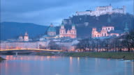 Wide shot time lapse traffic and clouds outside cathedrals at night / Salzburg