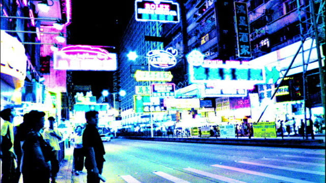 Wide shot time lapse traffic and pedestrians at crosswalk at night / neon lights in background / Hong Kong