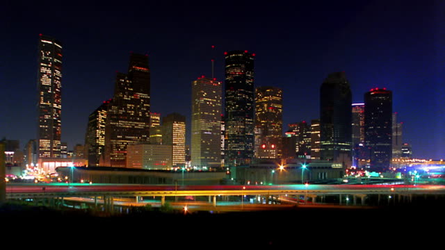 wide shot time lapse traffic on highway with houston skyline in background at night texas stock. Black Bedroom Furniture Sets. Home Design Ideas