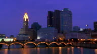 Wide shot time lapse traffic over bridge and Scioto River with Columbus skyline in background at dusk / Ohio