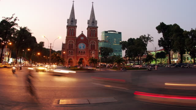 Wide shot time lapse traffic passing Notre Dame Cathedral from day to night / Ho Chi Minh City, Vietnam