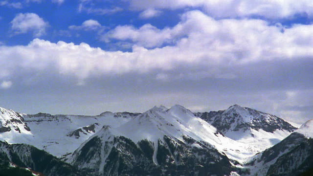 Wide shot time lapse white fluffy clouds in blue sky above snowy mountains / Rocky Mountains near Telluride, Colorado