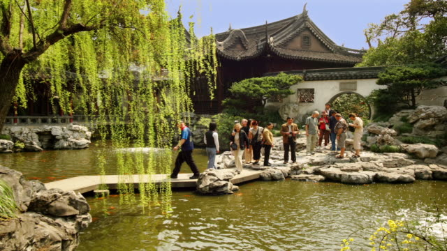 Wide shot tourists crossing footbridge over pond at Yuyuan Garden / Shanghai