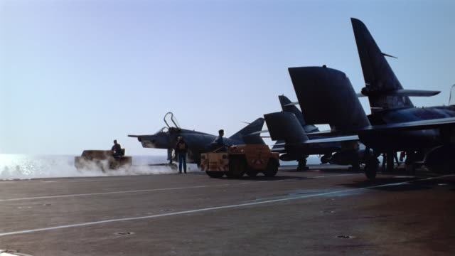 Wide shot tow carts pulling planes along runway of aircraft carrier