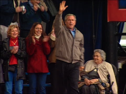2004 wide shot tracking shot Bush shaking hands with supporters and waving on stage at campaign rally / Hershey PA