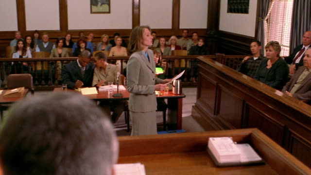 Wide shot tracking shot female lawyer approaching jury / back of judge's head in foreground / lawyer talking to jury
