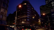 Wide shot traffic at intersection in front of apartment building on Greenwich Street at night / TriBeca, New York City