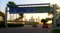 Wide shot traffic entering LAX airport area w/signs