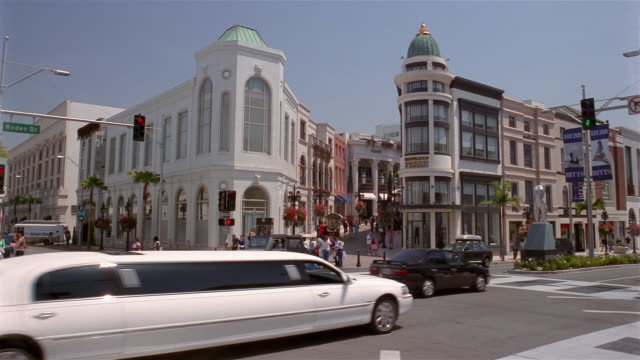 Wide shot traffic on Rodeo Drive / white stretch limousine in traffic / Beverly Hills, California