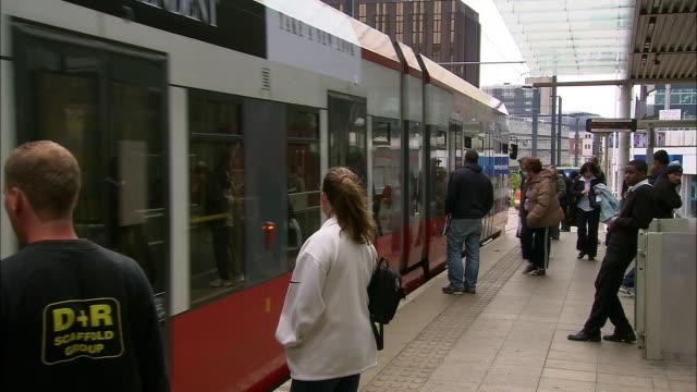 Wide shot tram pulling into East Croydon station / commuters getting on/off tram / London
