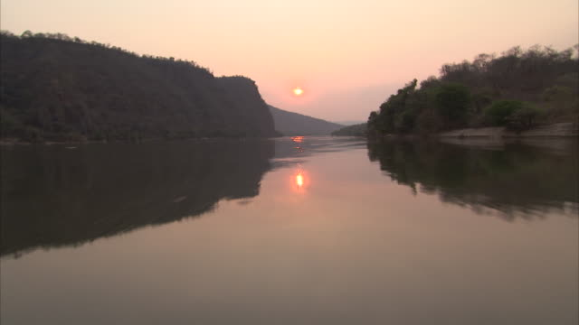 Wide shot travelling up Zambian river at sunset
