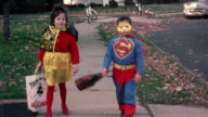 1965 wide shot trick or treaters in Halloween costumes (boy in Superman costume) walking on sidewalk