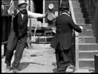 1918 B/W Wide shot two blindfolded men finding each other in alley, embracing, and dancing