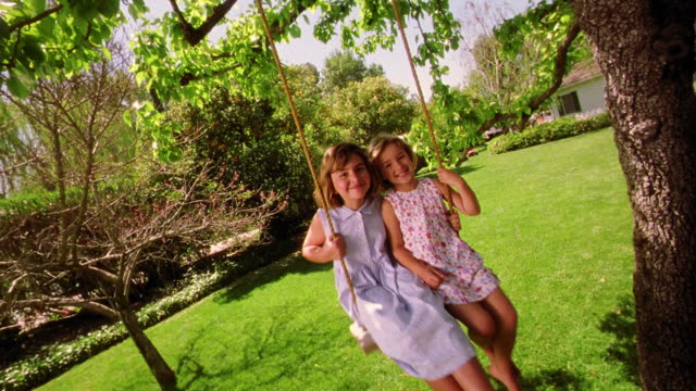 CANTED wide shot two girls swinging on tree swing toward camera smiling