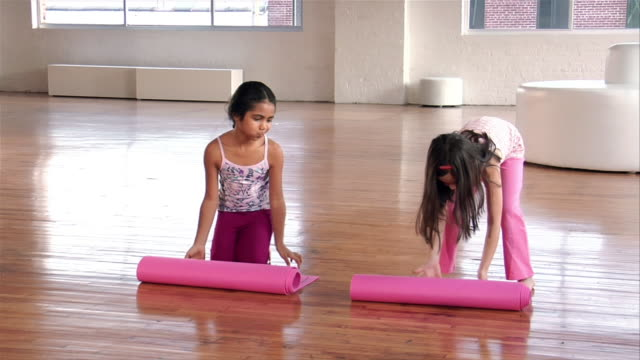 Wide shot two girls with exercise mats unrolling them on the floor and sitting down/ Brooklyn, New York