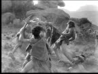 1914 B/W Wide shot Two groups of cavemen fighting with weapons during battle