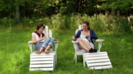 Wide shot two women sitting in adirondack chairs flipping through magazines and talking