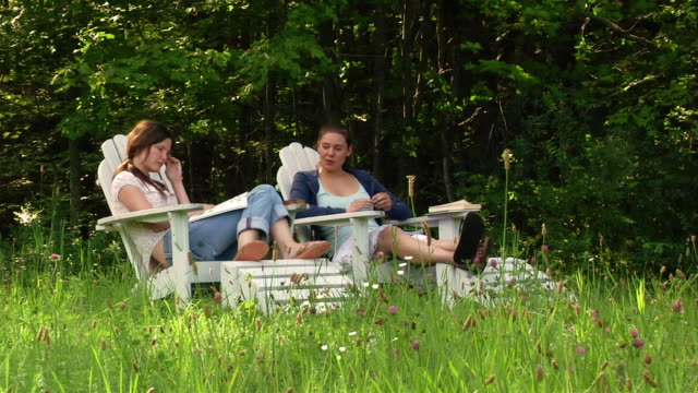 Wide shot two women sitting in adirondack chairs on edge of woods