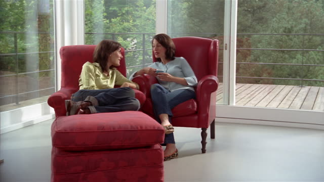Wide shot two women sitting in red armhairs by patio doors and talking