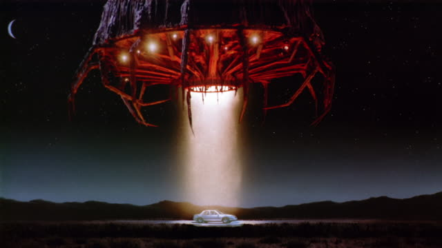 Wide shot UFO landing over and beaming tractor on car