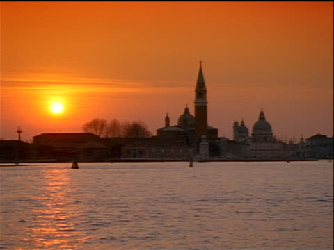 wide shot Venice skyline at sunset with water in foreground / Italy
