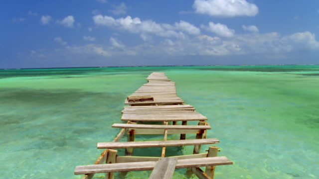 Wide shot view down length of damaged wooden pier in Caribbean Sea / Ambergris Caye, Belize