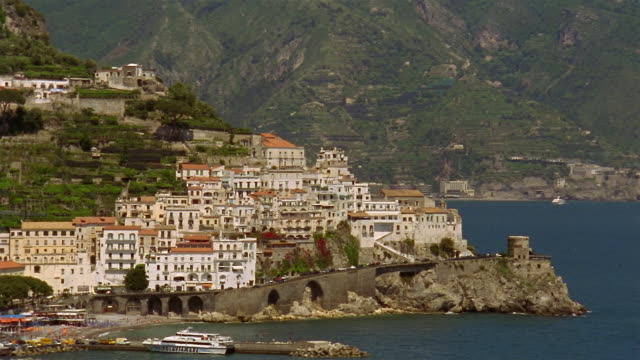 Wide shot view of hillside town of Amalfi with coastal road in foreground / Amalfi Coast, Campania, Italy