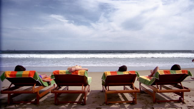 Wide shot waiter walking past people lying on beach in deck chairs with surf in background