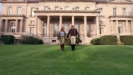 Wide shot wealthy couple in equestrian clothing holding hands and walking on lawn in front of mansion