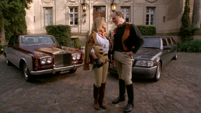 Wide shot wealthy man and woman in riding habits standing in front of luxury cars + mansion / looking at CAM