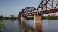 Wide shot with old railroad bridge over the Arkansas River, sunflowers and Bill Clinton Presidential Library in background